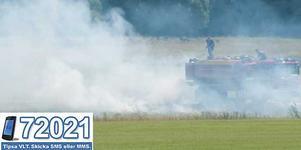 Brandmännen bekämpar gräsbranden från vattentankbilen.