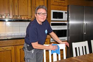 Sonja Andersson ger stolsryggarna i köket en omgång med trasan.