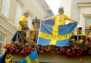 En Sandviken-flagga hängs upp av Victor Forsberg mot Slazburgs torg som är fullt av svenskar.