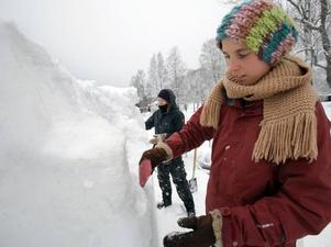 """saknade handskar. Karin Olsson konstaterade att gummihandskar hade suttit på sin plats. """"Jag är ganska blöt, men varm,"""" sa hon med ett leende och förklarade att hon tagit på sig långkalsonger, byxor och överdragsbyxor för att inte frysa. I bakgrunden står lagkompisen Tove Lindström och hackar fram en brunn."""