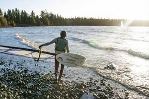 Morgan Näslund ger sig ut i vattnet för en ny tur på brädan. Kompisen Fredrik Olofsson har redan fått fart och styr mot Västervikens andra strand.