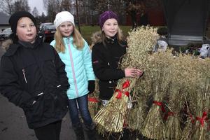 Albin Salåker, Nelly Karlsson och Tova Montin, klass 4 i Vikmanshyttan, har klätt sig rejält för en dag utomhus, som försäljare på julmarknaden.