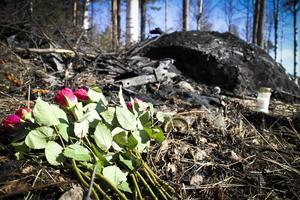 Rosor och ett minnesljus har ställts på platsen där olyckan skedde. Stora brännmärken syns på marken där bilen brunnit.