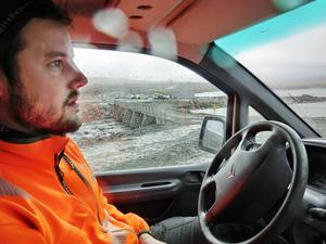 Mättekniker Oskar Karlsson från Peab, och i bakgrunden syns dammens utskovskanal.