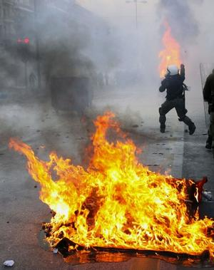 A riot policeman throw a stone at protesters during clashes in central Athens on Sunday, Dec. 7, 2008. Riots broke out Sunday in the Greek capital as demonstrators protested the fatal police shooting of a teenager in Athens the previous night. Youths hurled firebombs, rocks and other objects at riot police, who responded with tear gas. The circumstances surrounding the shooting of a 16-year-old boy by a police special guard in the downtown Athens district of Exarchia are still unclear. But the death triggered extensive riots in cities around the country overnight, with youths burning shops, setting up flaming barricades across streets and torching cars. (AP Photo/Thanassis Stavrakis)