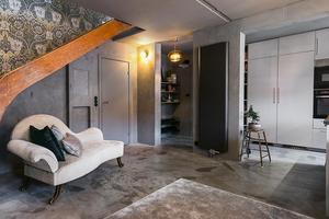Trätrappan i vintagestil leder upp till ovanvåningen som är inredd i ljusare färger. Till och med dörrarna är målade i samma sobra gråkulör.