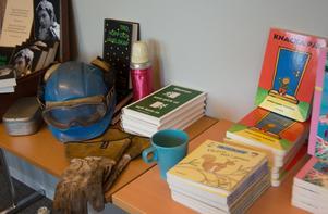 Hjälm. matdosa och arbetshandskar är attribut för en arbetare - och det är också boken. Eller borde vara, med tanke på arbetarlitteraturens stolta tradition.