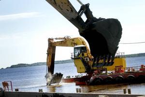 13,5 METER DJUPT. Grävmaskinen ute i vattnet vid Fredrikskans skopar upp gyttjig lera och sten från havsbotten på en pråm. 13,5 meter ska djupet bli i Gävle hamn. Det som man muddrar för nu är fundamenten till kajerna.