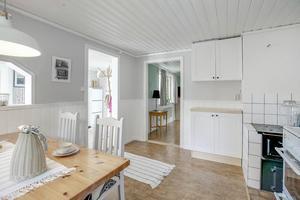 Köket har vit inredning, vedspis och plats för bord och stolar. Foto: Svensk Fastighetsförmedling.