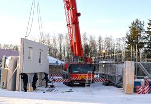 Med hjälp av en mobilkran lyfts ett väggelement till ett av de nya hyreshusen på plats.