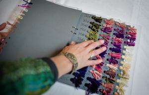 I den plan som Eva Olanders skickade med sin ansökan ingår garnprover och garnberäkningar. Varje garntuss innehåller flera trådar av olika kvalitet och färg för att ge ytan på den slutgiltiga väven ett  levande uttryck.