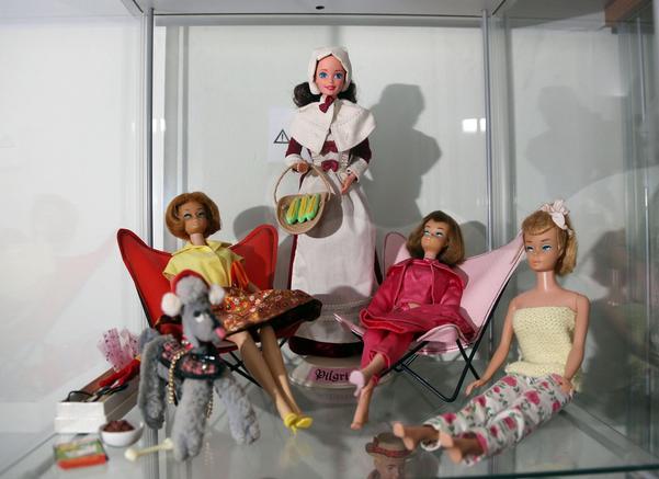 Två Barbie vilar i fladdermusfåtöljer. Barbie som sitter på hyllan är köpt på loppis och bär hemsydda kläder. Den stående dockan är norsk.