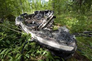 Den utbrända båten som kommunen vill att Tomas Balkefors ska forsla bort låg tidigare i vattnet i flera år. Nu ligger den en bit upp i skogen.