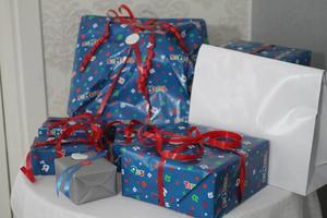 En hög med presenter väntar på att öppnas av barnen.