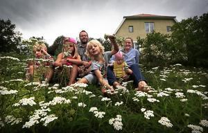 Malte, Alice, Per, Elis, Ture och Sandra i ett hav av röllekor som står i blom nedanför huset.