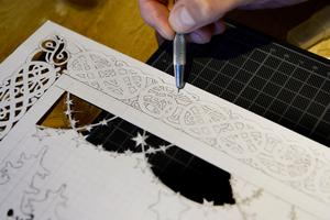 Petra Staav använder en skalpell för att skära i papperet.