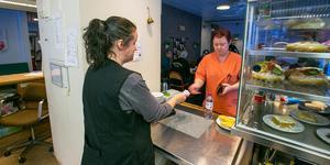Här köper undersköterskan Viktoria Garefelt som jobbar på äldreboendet i Backe sjukhusbyggnaden mineralvatten av Karin Eriksson, en av tre som jobbar i Café Violen.