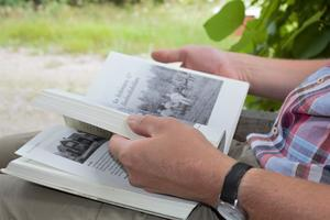 Erik Pettersson bläddrar i boken Norr Salbo by & Westmanlands Regemente.