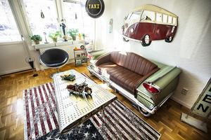 En del av en flygplansvinge till bord, en VW-buss i plåt på väggen och soffan som är bakdelen på en äkta Oldsmobile från 1959 pryder vardagsrummet. Notera den gamla upplysta TAXI skylten. Är man entusiast så är man.