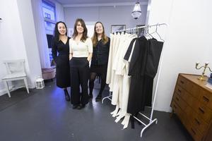 På bilden bär Johanna Mörk och Tini Warg kläder ur kollektionen. På ställningen hänger provkläder som kunder får testa innan det personliga plagget sys efter rätt mått och önskemål.
