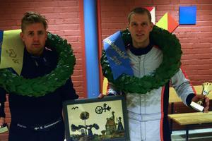 Erik Gustafsson (till vänster) och Mattias Jirvelius (till höger) håller segerpokalerna i ena handen. I den andra håller de tavlan som förkunnar att de vann sträckan som kallas Björnjägarens minne.