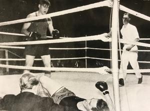 På väg mot JSM-final i lätt tungvikt 1946 i Eriksdalshallen – Olle Axelsson. Med en perfekt höger har den 21-årige västeråsaren träffat sin motståndare från BK Linnea, Karl-Åke Hagström. Denne är på väg mellan repen och hindras av en funktionär att ramla ner från ringgolvet.