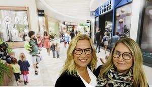 Centrumchef Anette Lättman och marknadskoordinator Maria Sörling framför en illustration om det nya Valbo Köpcentrum som växer fram under tre år.