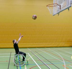 Det är förstås betydligt svårare för en rullstolsbasketspelare att träffa korgen än en stående spelare. Henrik får längre avstånd till ringen som sitter på drygt 3 meter, och kan ju inte heller hoppa! Foto: Jon Norberg