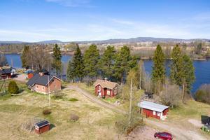 Gård med strandtomt vid älven i Södersätra med många möjligheter, ekonomibyggnader med både verkstad och stall. Det finns också ett gästhus med sommarkök. Fastigheten har strandtomt. Foto: Patrik Persson.