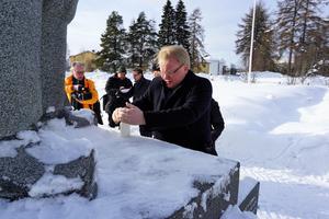 Sverige försvarsminister, bördig från Borlänge men också från Kuusamo, tänder ett ljust vid ett minnesmonument över andra världskrigets. Foto: Börje  Forslund