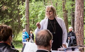"""Eva Lind dirigerar Falu blåsorkester. """"När hon viftar mycket så kallar vi henne Veva"""" skojar presentatören."""
