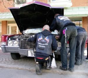 Medlemmar ur Labbås Cruisers tar en närmare titt på i en motorhuv.