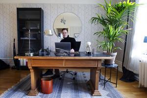 Björns kontor har ett robust, antikt skrivbord. Men också ett höj- och sänkbart skrivbord i andra delen av rummet.