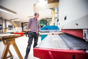 Åke Wickman är en av de anställda på Wikners i Persåsen. Här övervakar han ett par delar till ett ekbord som ska köras genom bandputsen.