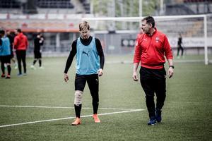 Daniel Björnquist linkar av lördagens träning i sällskap med sjukgymnasten Peter Brolin. Hårt lindad om höger knä.