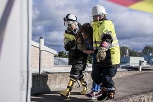Här tränar två personer ur räddningsstyrkan en av de frivilliga skademarkörerna att ta sig till säkerhet efter helikopterkraschen.