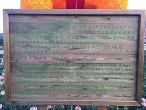 """Den förklarande skylten framför bocken, gröntonad text på mörkspräcklig botten. """"Gävlebocken är 13 meter hög, 7 meter lång och väger 3 ton… Gävle är en smart stad med hög livskvalitet… Gävlebocken (---) symboliserar den okuvliga anda som återfinns hos folket."""""""