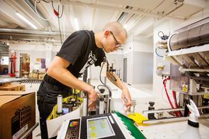 Björn Appell gör i ordning etikettmaskinen. Snart skall en batch ölflaskor etiketteras.