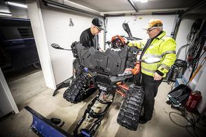 Rune Göransson och Ulf Backberg, skruvar på den maskin de har för att pista områdets snöskoterleder. I dag får den lite bättre belysning så lederna kan prepareras när mörkrets inbrott kommit.