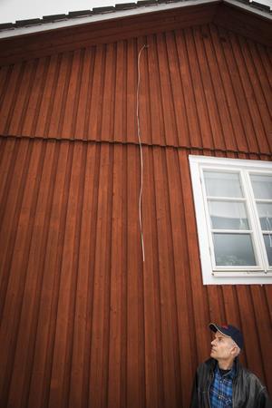 Kabeln som tidigare gick mellan en stolpe på gården och huset hänger nu längs den rödmålade väggen.