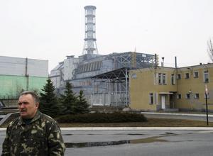 En man från ukrainska räddningstjänsten framför sarkofagen över reaktor 4 i Tjernobyl. Foto: Henrik Montgomery /TT