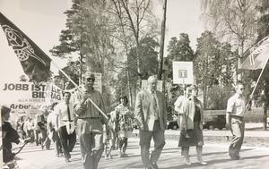 1 maj i Surahammar 1983. Arbete åt alla. Första majdemonstrationen i Sura lockade bortåt 300 människor. Kraven var bland annat en annan regering och statliga jobb åt arbetslösa. I mitten går Sven Erik Gårdhage.