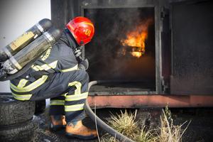 En av instruktörerna styr gasolkranen som reglerar hur mycket det ska brinna under övningen.