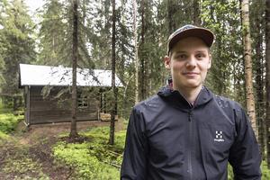 Nils med stugan mitt i skogen i bakgrunden.