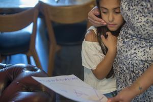 Lin visar upp vad hon skrivit för mamma Amira.