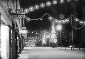 Julpyntat på Prästgatan där den löper genom Stortorget. Till vänster Lundins kläder och G Perssons trafikskola. Troligen  från 1940- eller 1950-tal. Fotograf: ÖP arkiv