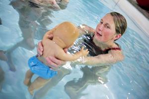 Instruktören Camilla Moberg visar hur föräldrarna ska hantera sina barn i vattnet.