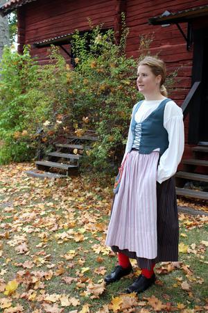 Sara Agemark med Ösmodräkten framför visthusboden från 1823. Foto: Ulla Laiho
