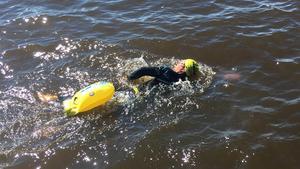 Simon Zmrzlak simmar iväg längs strandkanten vid Lögastrand. Dagens pass består av cirka en kilometer simning under lunchen.