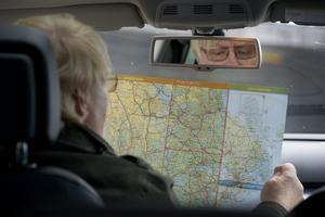 En man studerar vägkarta i bil. I framtiden kan kommuner bli färre men större, bland annat på kartor. Foto: Janerik Henriksson / TT.